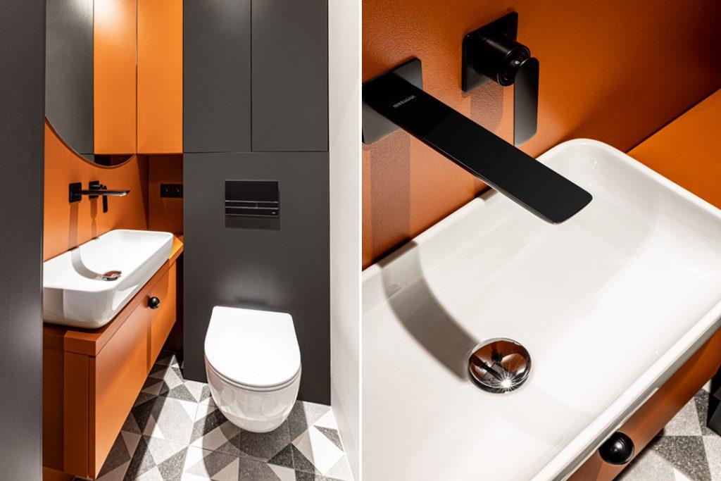 W niewielkiej toalecie króluje czerń i soczysty kolor pomarańczy