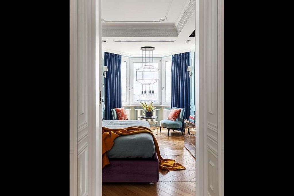 Zaaranżowany przy oknie wykuszowym kącik kawowy akcentuje lekka, geometryczna lampa.