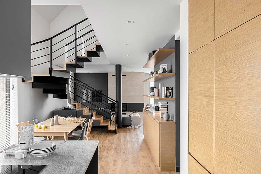 Dom blisko natury - aneks kuchenny i jadalnia przy schodach dywanowych