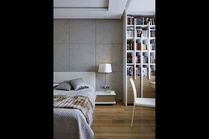 biała biblioteczka zdrewnianymi wstawkami umieszczona w sypialni