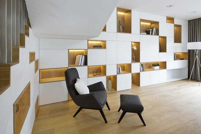 biała zabudowa zkontrastowymi podświetlanymi półkami doeksponowania książek