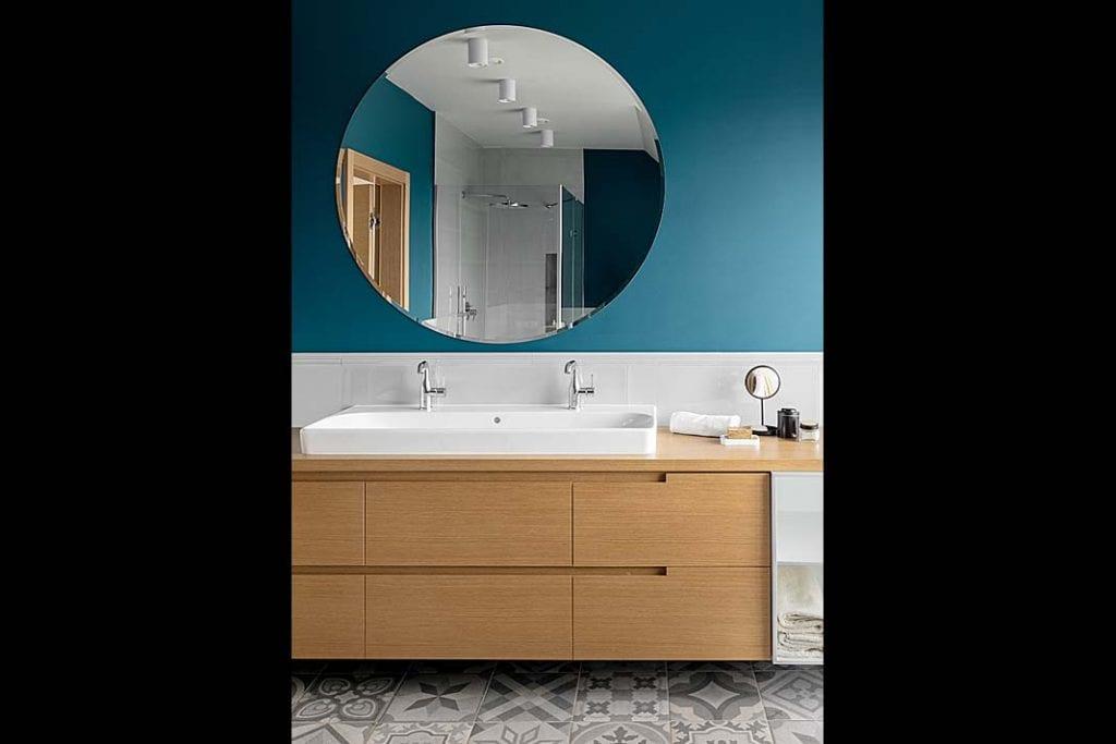elegancka umywalka i duże okrągłe lustro na ścianie w łazience