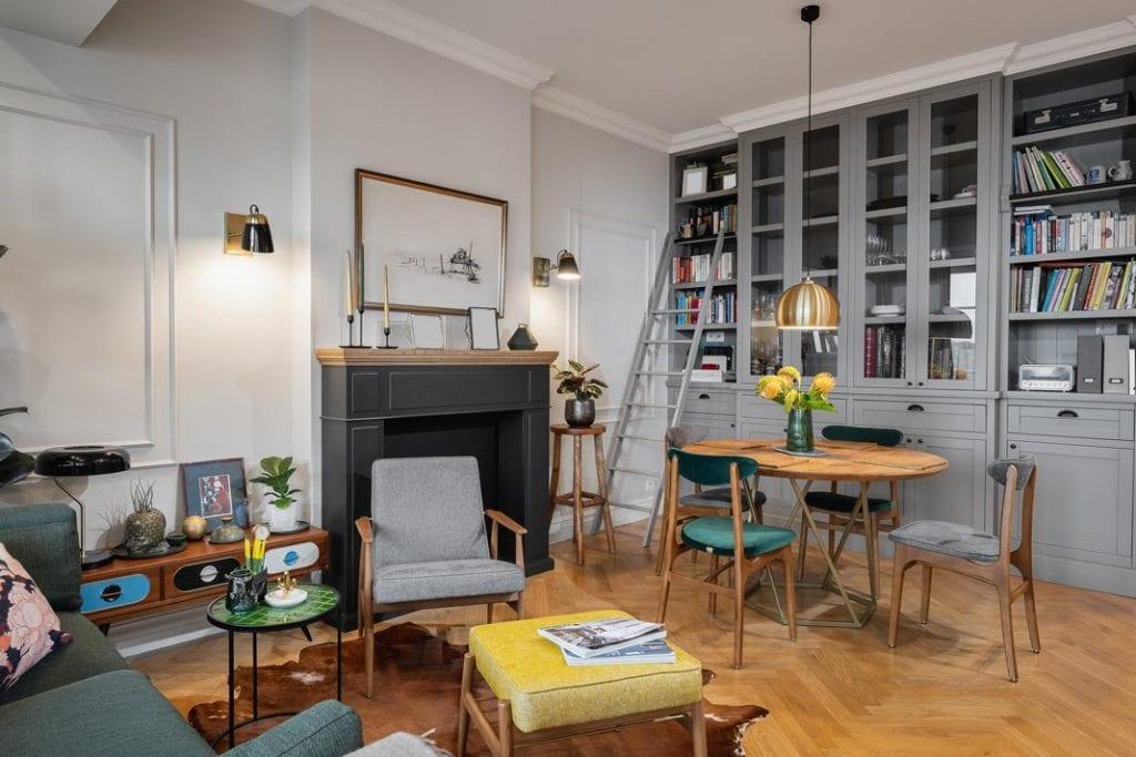 Funkcjonalne mieszkanie dla rodziny. Klimatyczny salon z przeszkloną biblioteczką, stylowymi meblami i portalem imitującym kominek.