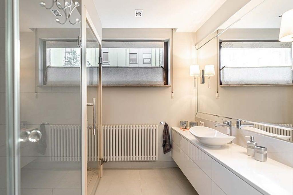 Salon kąpielowy oświetlony kinkietami.