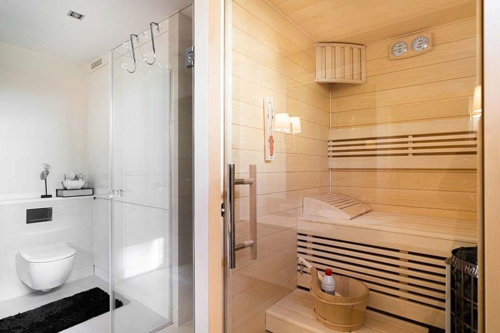 Wnętrze sauny widoczne za przeszklonymi drzwiami.