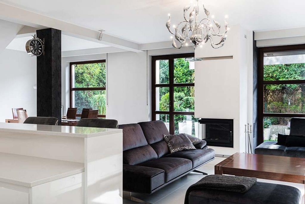 Nowoczesny glamour. Wnętrze salonu z kominkiem i sofą