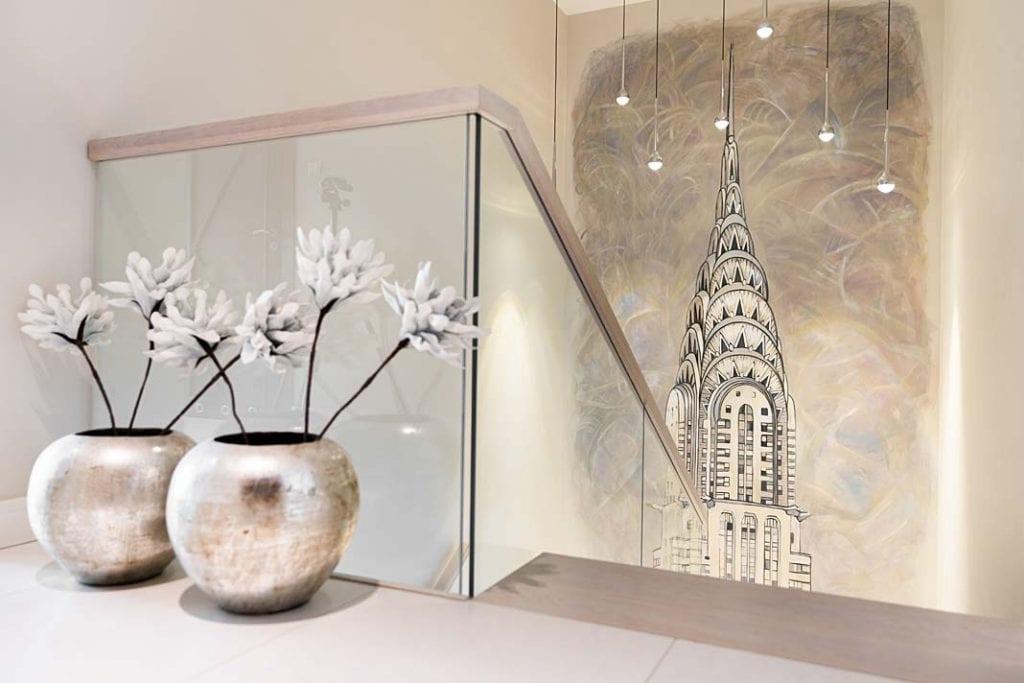 Schody ze szklaną poręczą. Na ścianie grafika nowojorskiego wierzowca.
