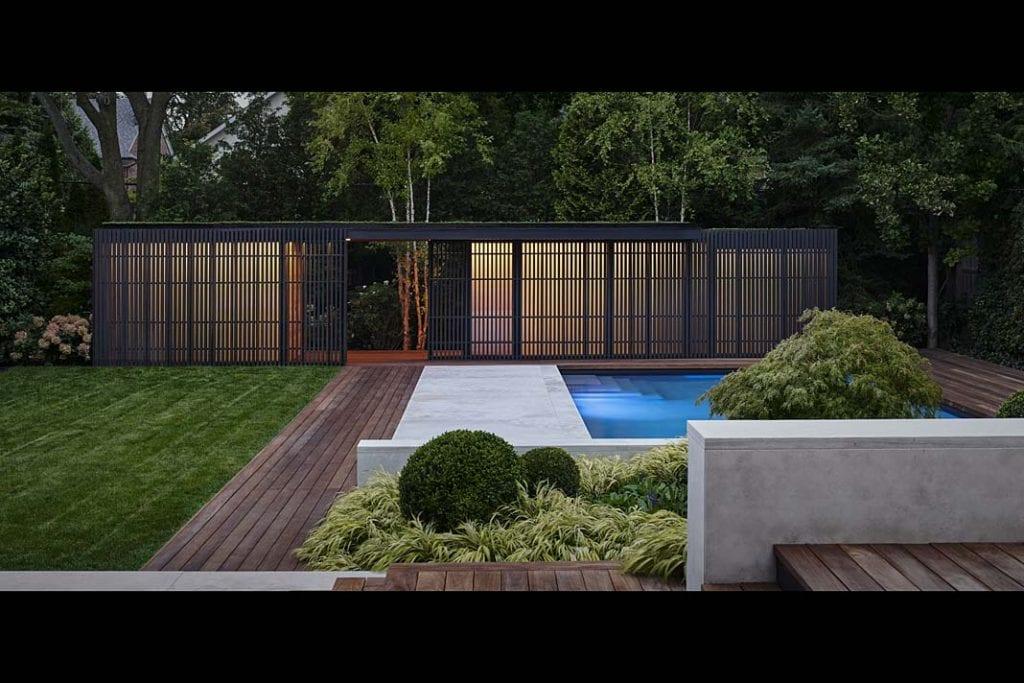 Widok na pawilon ogrodowy w ogrodzie z basenem.