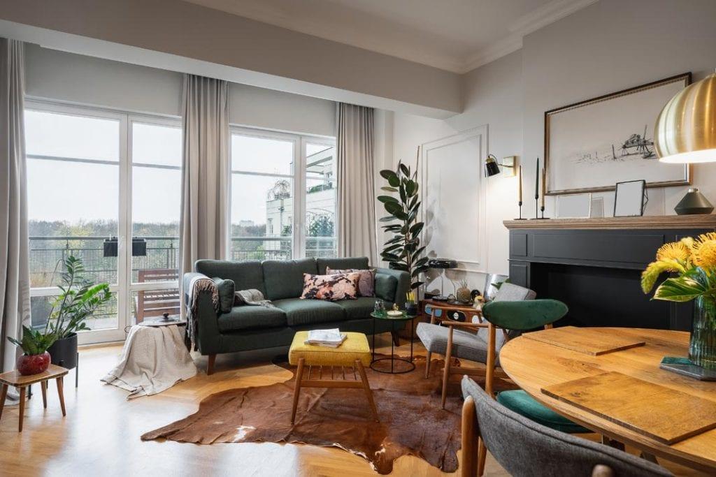 Funkcjonalne mieszkanie dla rodziny. Przytulny salon, duże okna i krzesła z welwetową tapicerką.