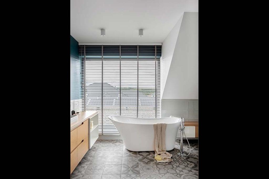 Dom blisko natury. Salon kąpielowy z ogromnym oknem i wolno stojącą wanną marki Excellent