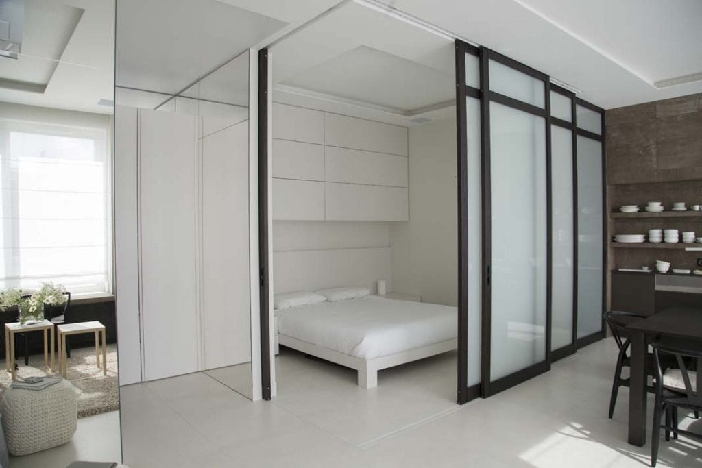 Sypialnia w salonie wydzielona przy pomocy drzwi przesuwnych (fot. Studio O)