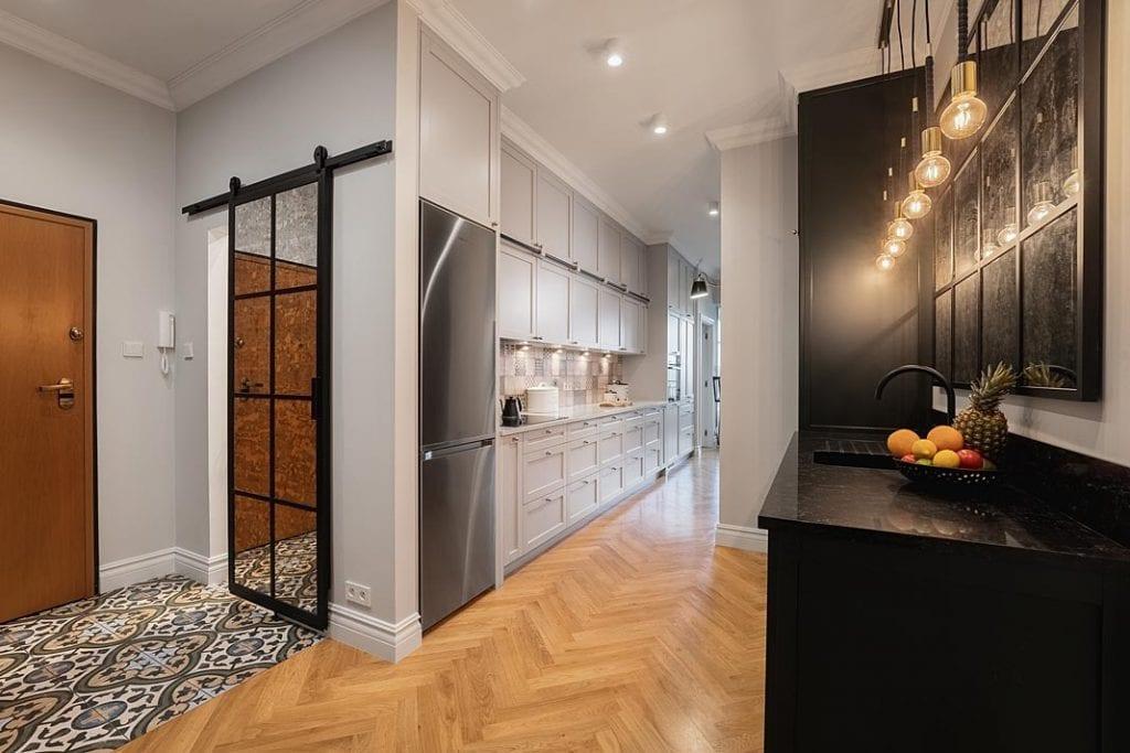 Funkcjonalne mieszkanie dla rodziny. W strefie wejściowej lustro ze szprosami pełniące funkcję przesuwnych drzwi do garderoby.