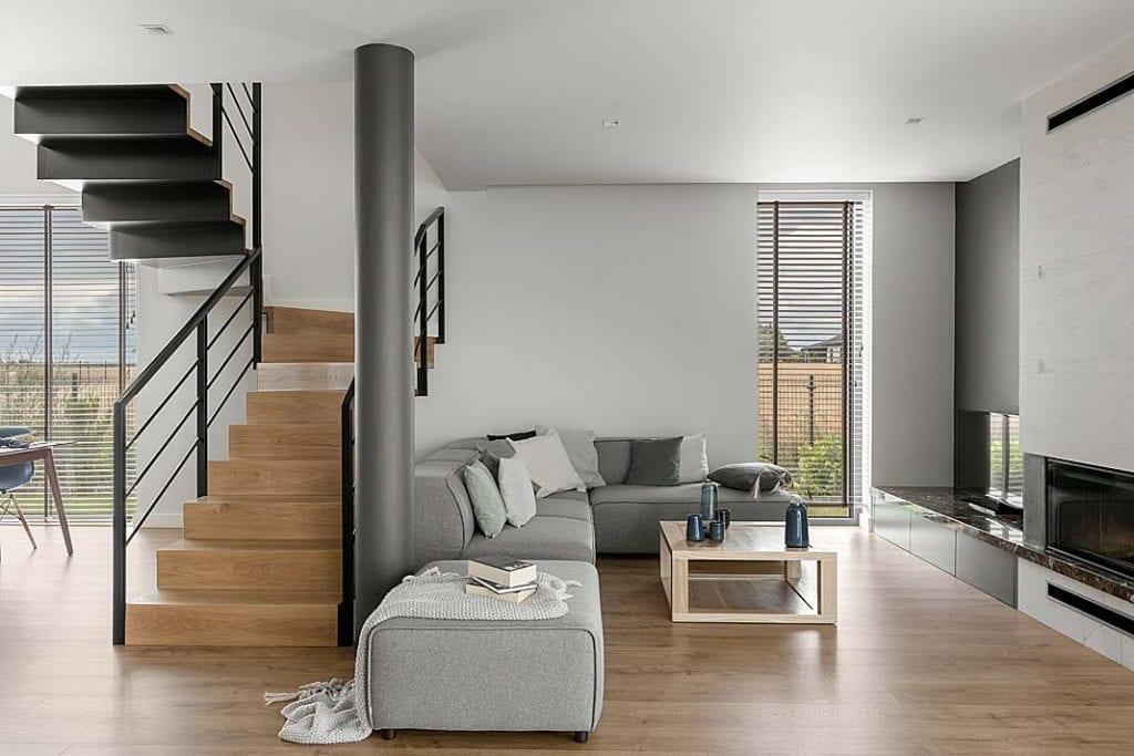 Dom blisko natury - wygodna sofa i stonowane kolory oraz ozdobiony marmurem kominek