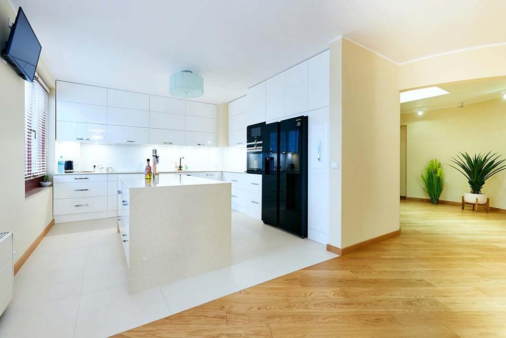 Połączenie podłogi drewnianej z gresem ułożonym w aneksie kuchennym.