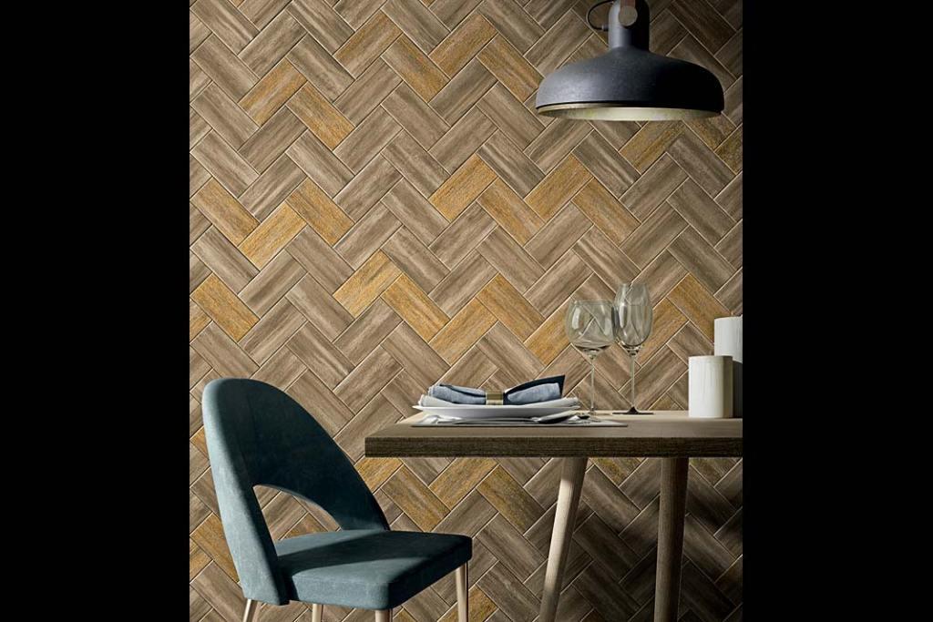Ściana z płytkami imitującymi drewno ułożonymi w modny wzór jodła angielska.