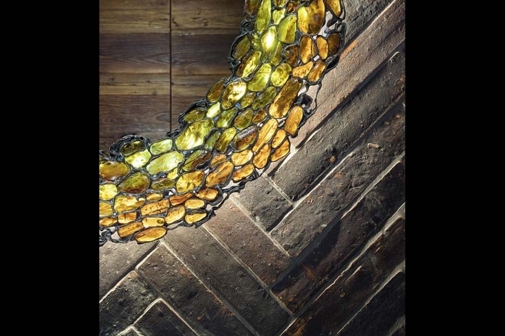 Zbliżenie na ścianę łazienki, na której płytki zostały ułożone w jodełkę.