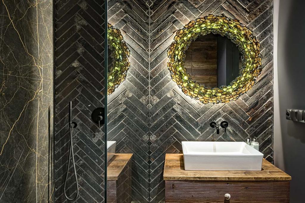 Łazienka z płytkami na ścianie ułożonymi w jodełkę.