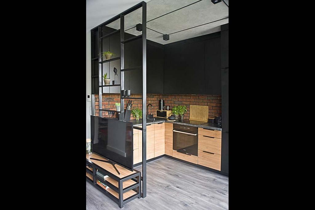 część kuchenna oddzielona od salonu ażurową ścianką ze stali w czarnym kolorze