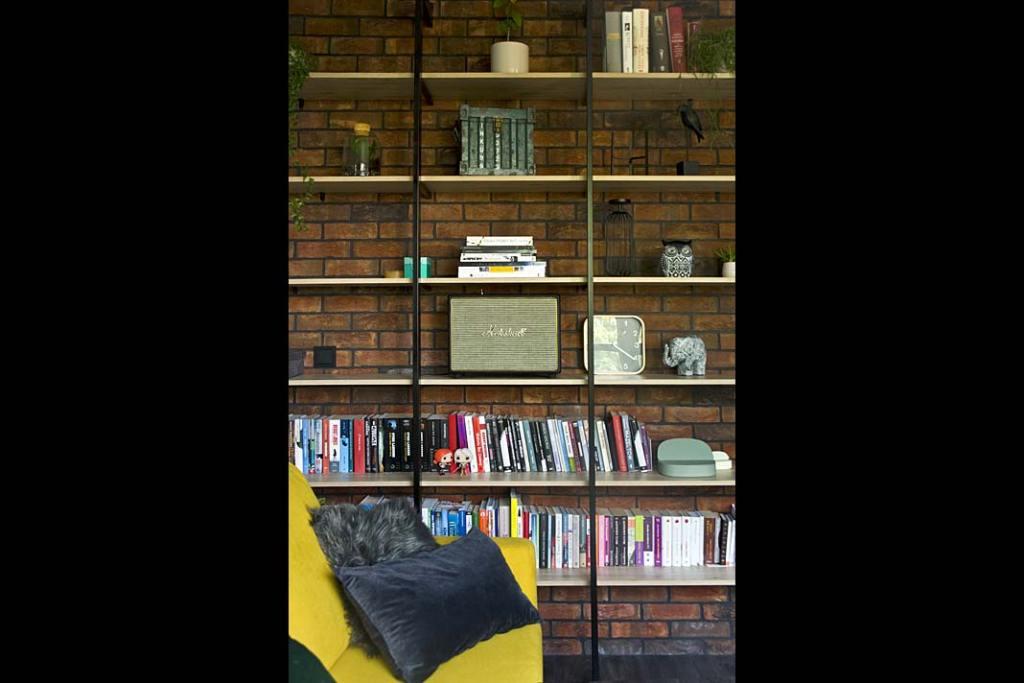 domowa kolekcja książek i pamiątek na prostym regale w loftowym stylu