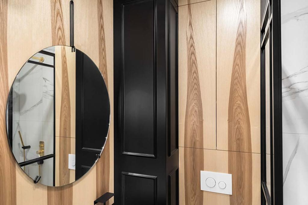 łazienka wykończona panelami jesionowymi i okrągłe lustro