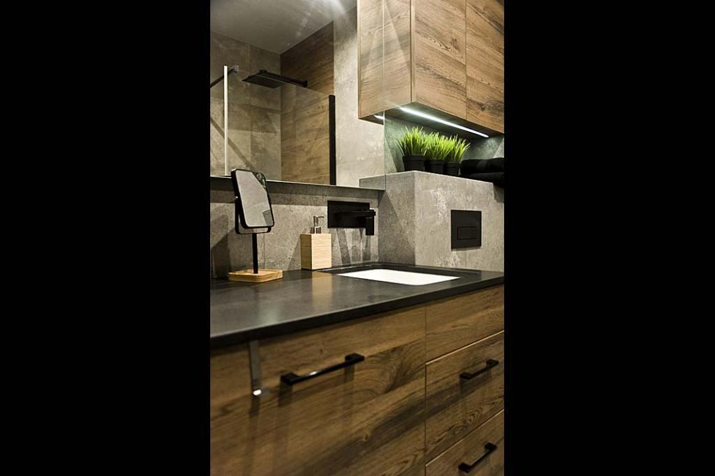 łazienka z płytkami przypominającymi surowy beton i wykonane z drewna meble