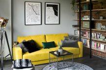 musztardowa sofa w salonie urządzonym w loftowym stylu