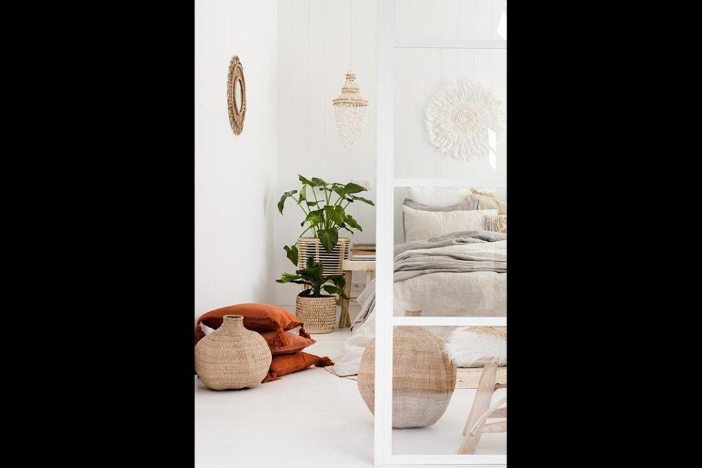 Przytulna sypialnia w stylu white boho - lniana pościel, białe ściany i kolorowe poduszki na podłodze
