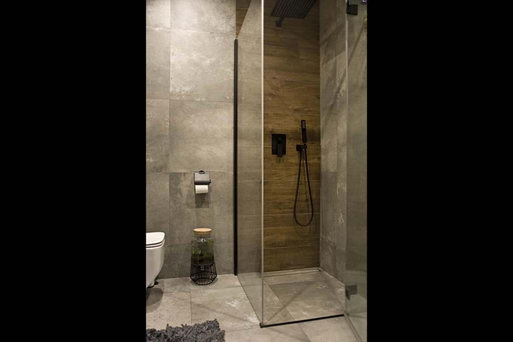 szklana kabina prysznicowa w łazience urządzonej w stylu industrialnym