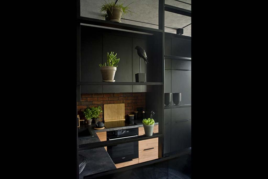 wykonane ze stali czarne ażurowe przepierzenie pomiędzy częścią kuchenną a salonem