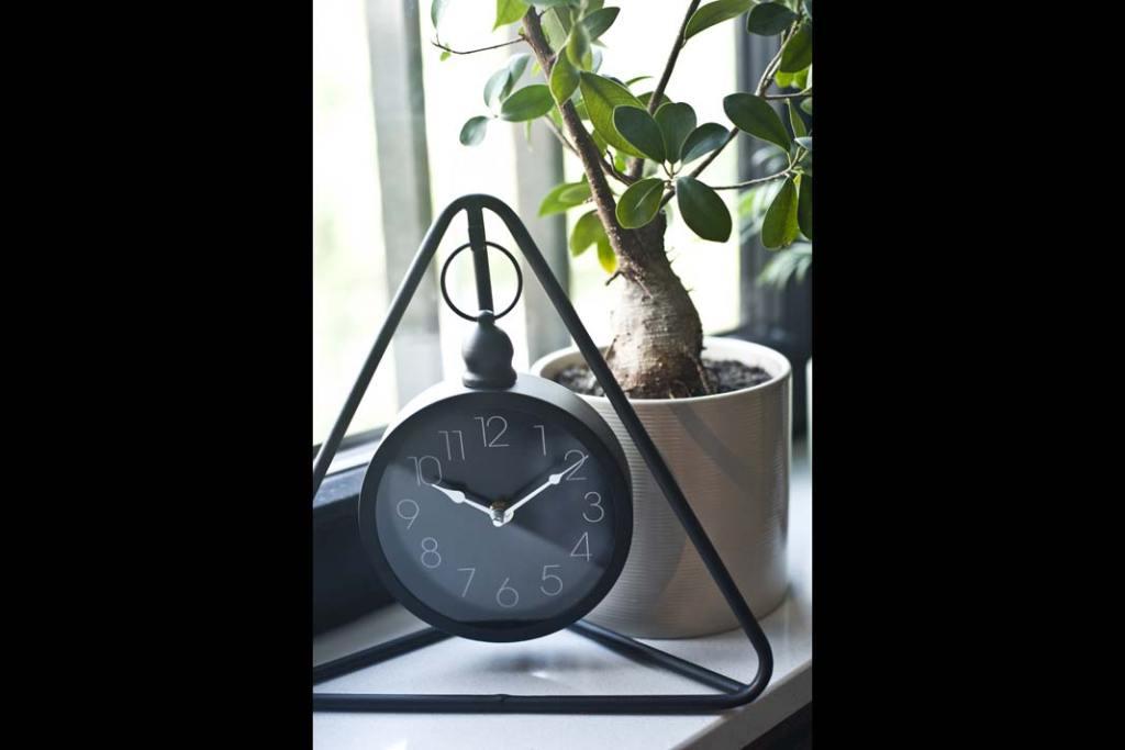 czarny zegar na parapecie, jako element wyposażenia w loftowym stylu