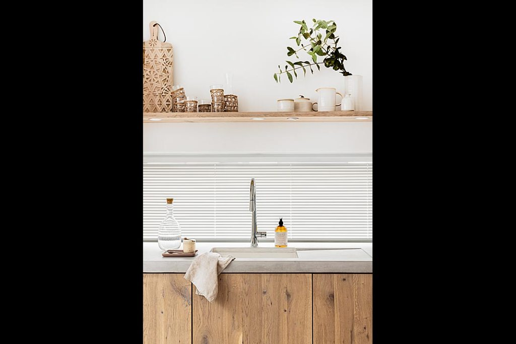 zlew kuchenny przy oknie, szafki i półki z naturalnego drewna, blat kuchenny z mikrocementu