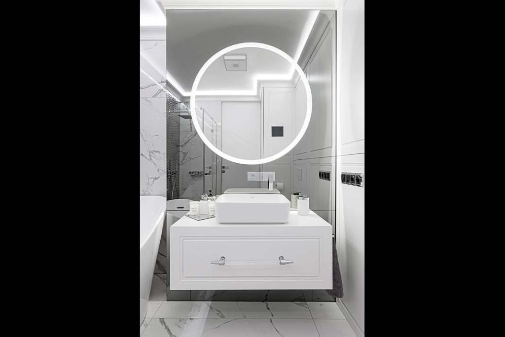 Lustrzana ściana iokrągłe lustro zpodświetleniem ledowym dodają łazience głębi.