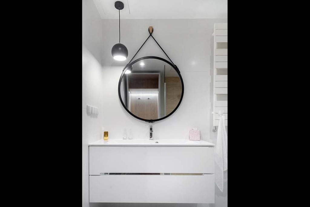 Apartament w stylu skandynawskim okrągłe lustro nad szafką w łazience