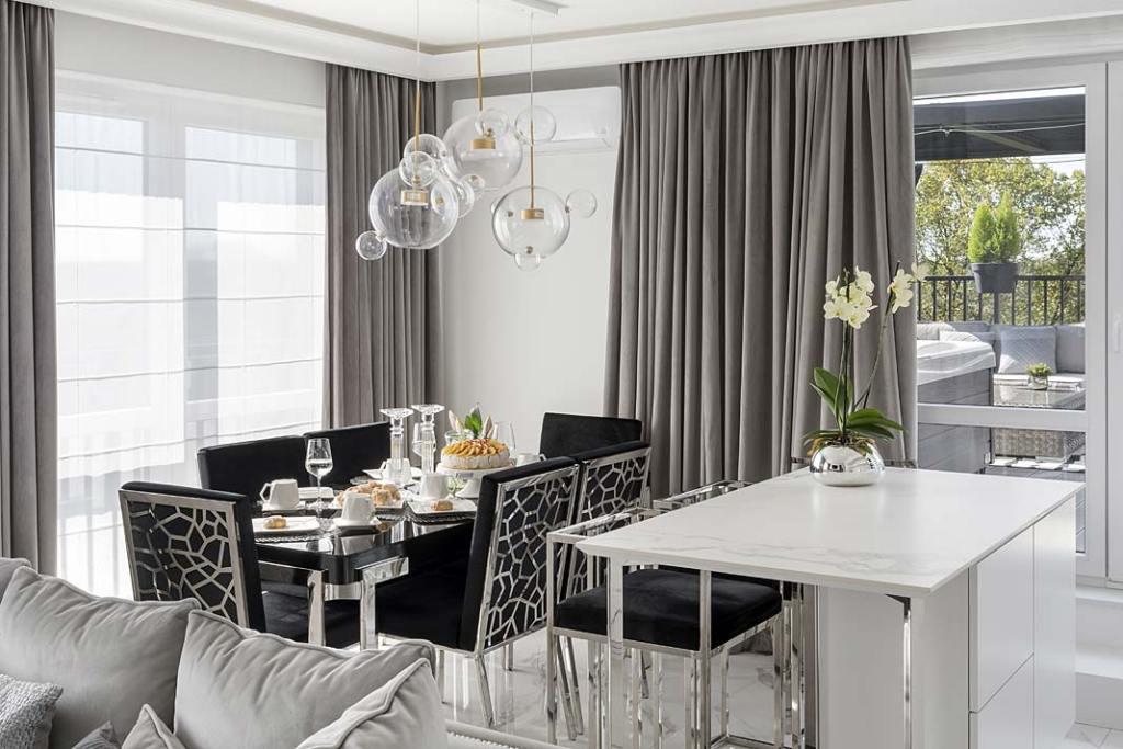 Część dzienna apartamentu w stylu glamour tootwarta przestrzeń zkuchnią, jadalnią istrefą wypoczynku