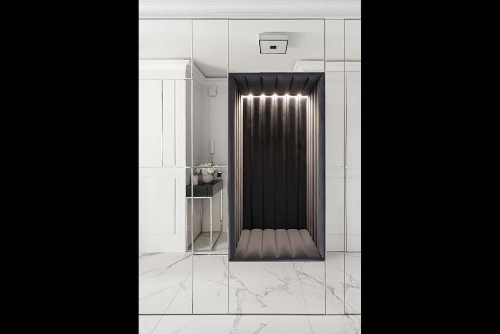 Podświetlana wnęka, wyłożona welurem topraktyczny inietuzinkowy pomysł naaranżację przestrzeni korytarza.