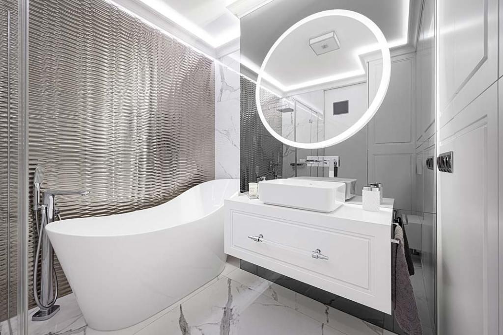 Salon kąpielowy w stylu glamour i wolno stojąca wanna na tle srebrzystej ściany