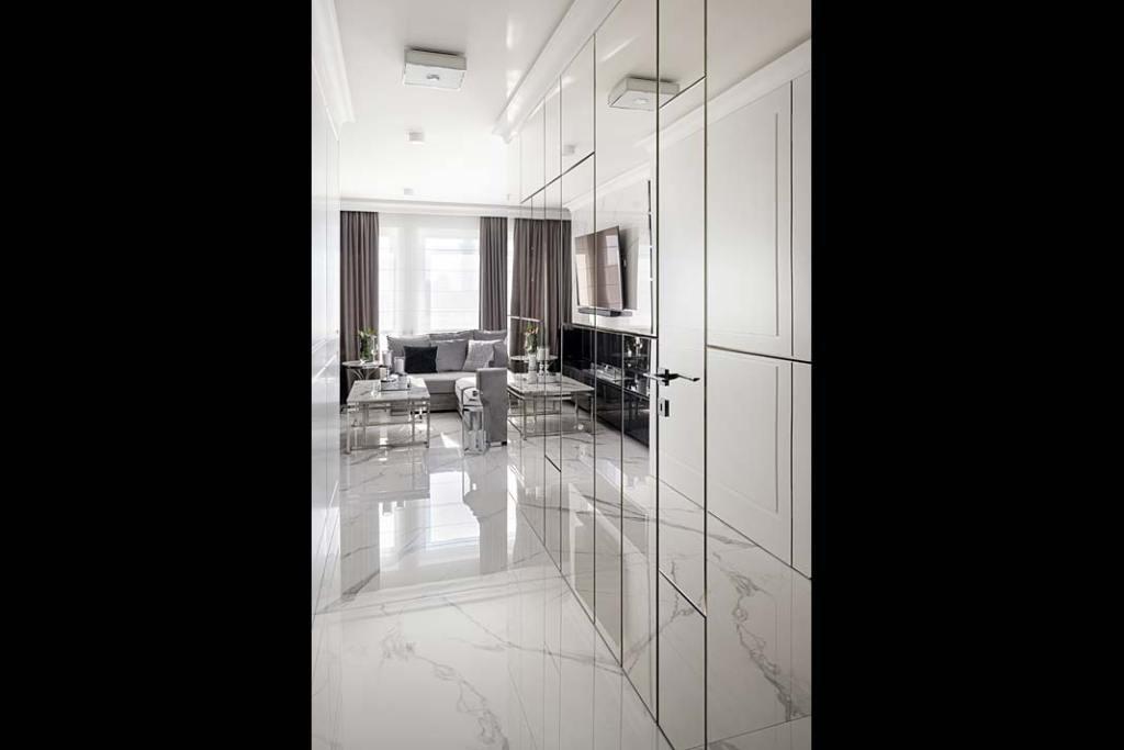 Styl glamour i ściana w korytarzu ozdobiona fazowanymi lustrami z trudno dostrzegalnymi ukrytymi drzwiami