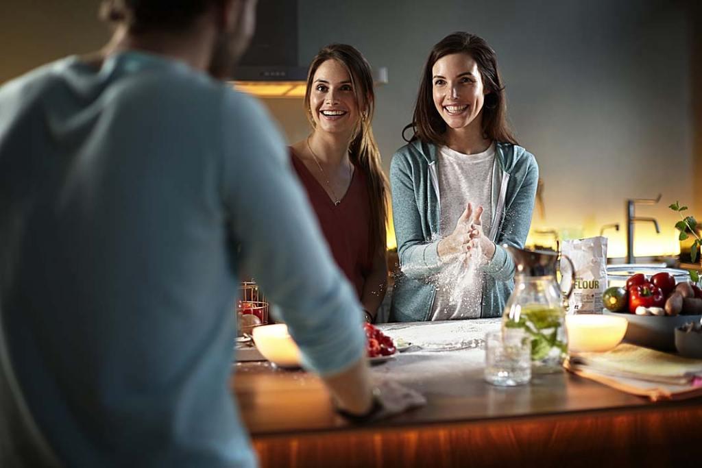 trzy osoby w kuchni oświetlonej lampami Philips HUE GO stwórz przytulną i komfortową atmosferę