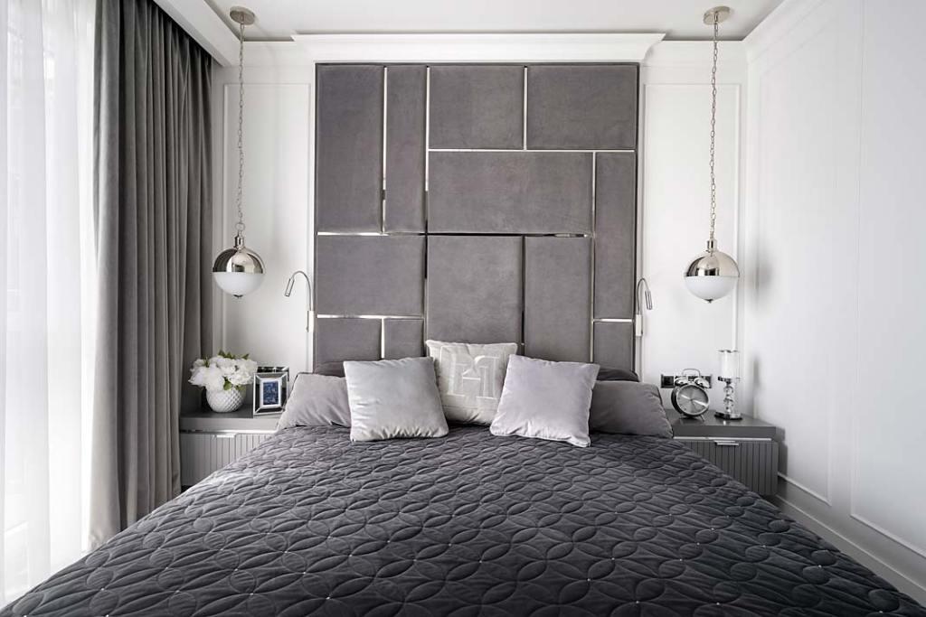 W sypialni uwagę zwraca zagłówek wykonany z miękkich paneli poprzecinanych chromowanymi listwami.