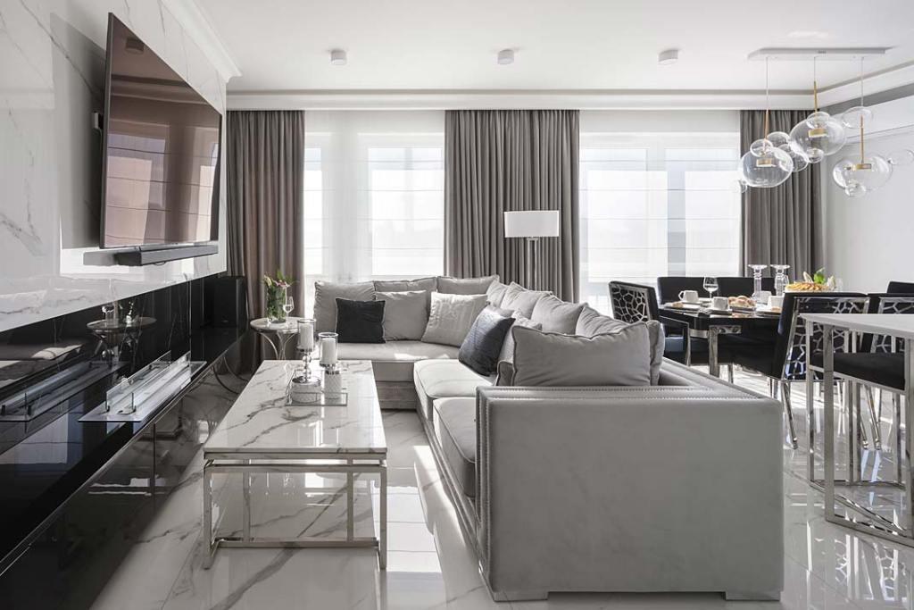 Otwarta przestrzeń zkuchnią, jadalnią istrefą wypoczynku to część dzienna apartamentu urządzonego w stylu glamour.