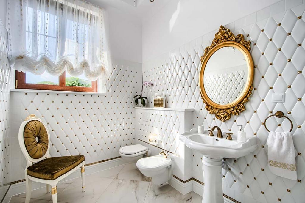 Biała łazienka w klasycznym stylu ze złotymi dodatkami.