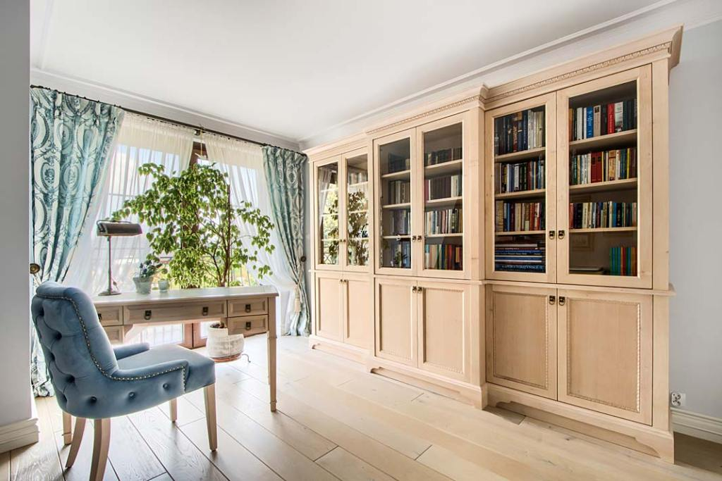 Gabinet z ręcznie wykonanym drewnianym biurkiem i biblioteką