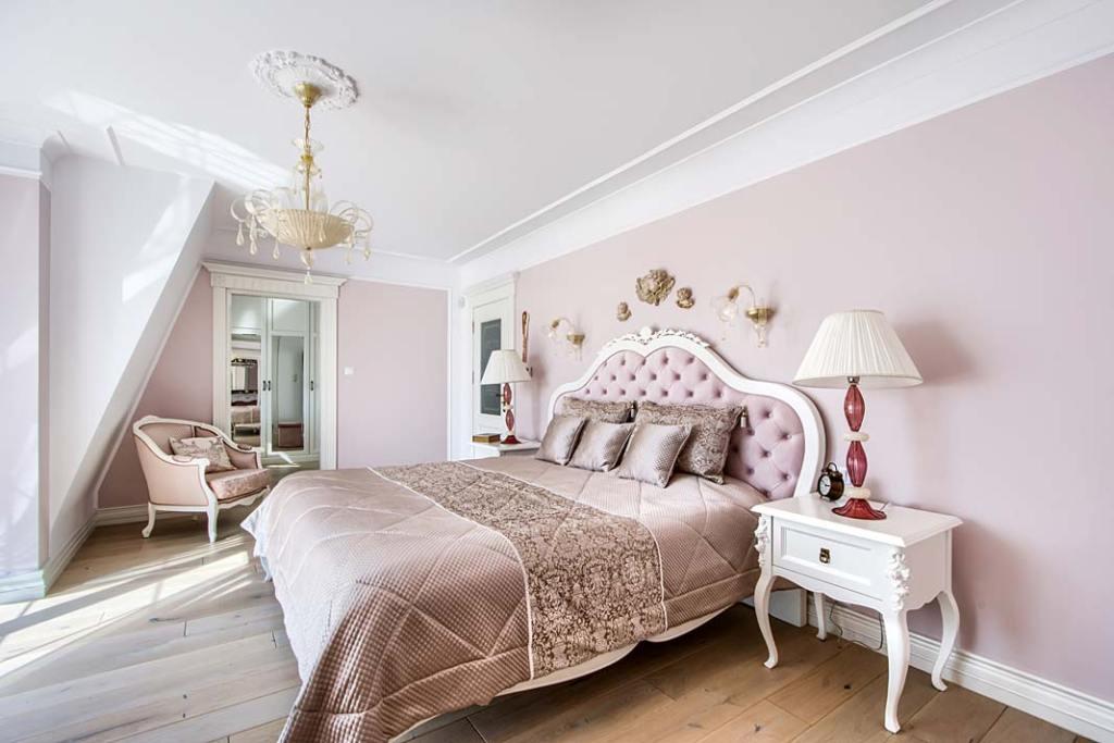 Klasyczna sypialnia z drewnianym tapicerowanym łóżkiem.