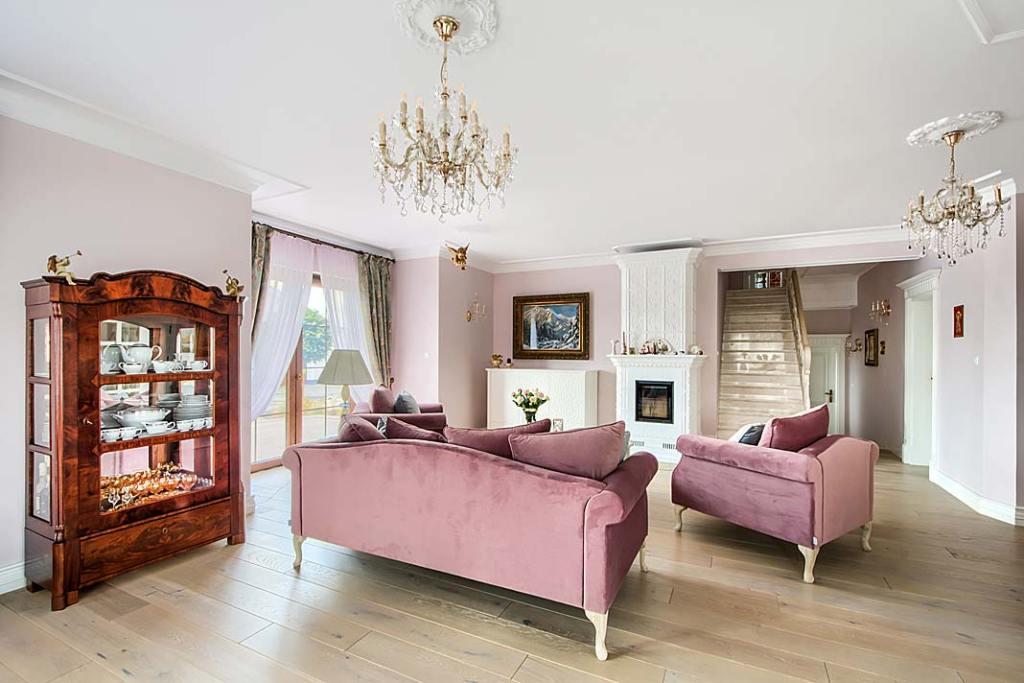 Salon urządzony w klasycznym stylu,w głębi biały kominek z ręcznie robionych kafli.