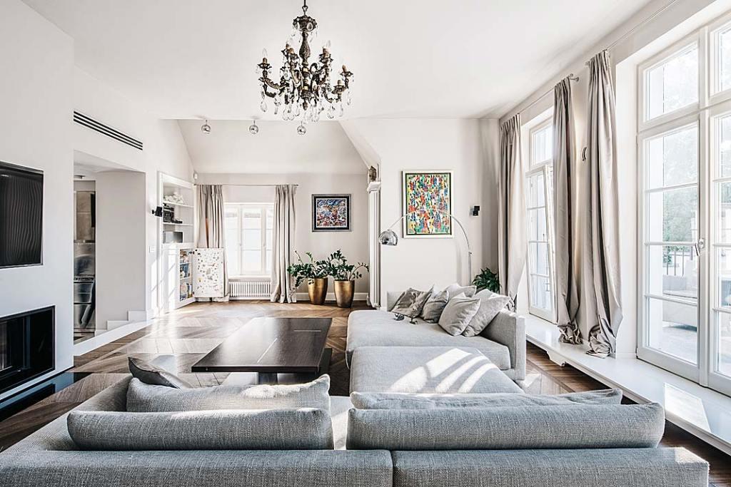 Przestronny salon utrzymany jest w stonowanej kolorystyce. Zdobią go obrazy i stylowe meble