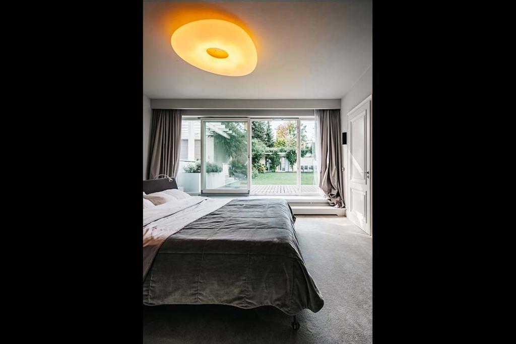 Sypialnia z wyjściem i widokiem na ogród w willi na Bielanach.