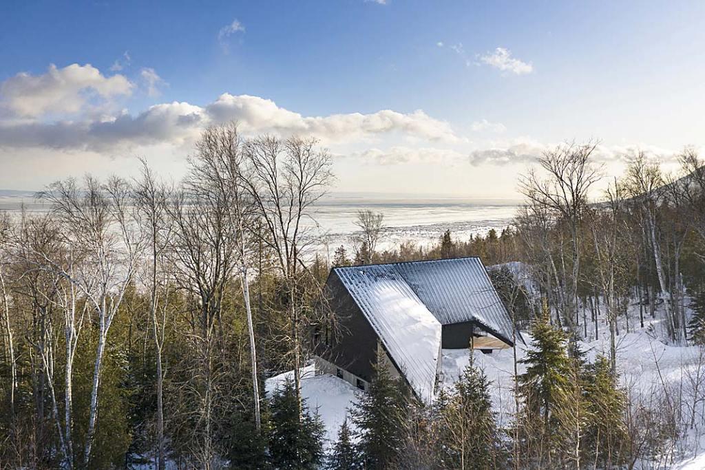 Cabin A, całoroczny dom letniskowy. Od strony ulicy dach schodzi aż do ziemi