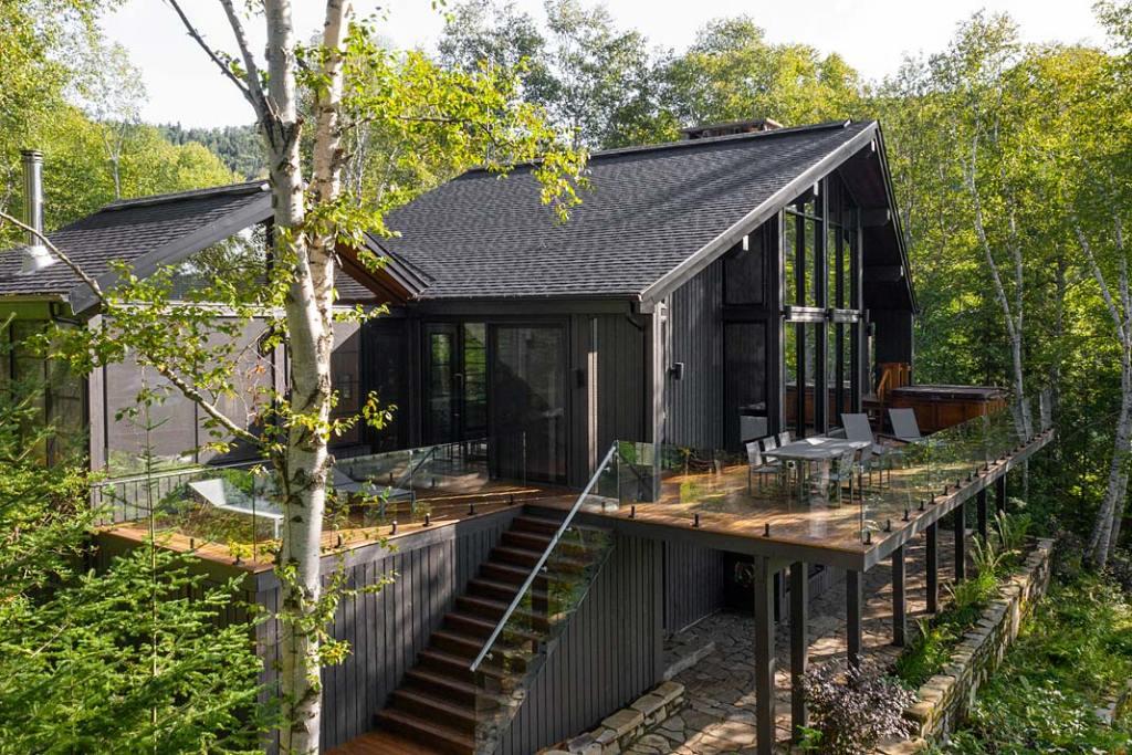 Nowoczesny, drewniany dom po modernizacji ma dwa tarasy i zadaszone patio