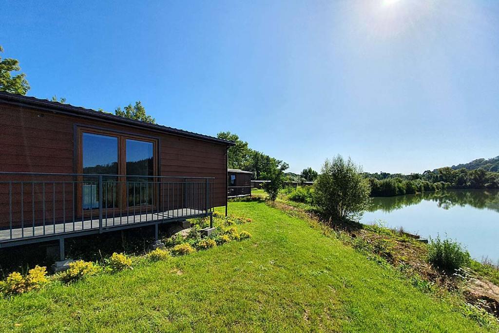Domy mobilne. Domek nad jeziorem, na elewacji okładzina Kerrafront Wood Design firmy Vox