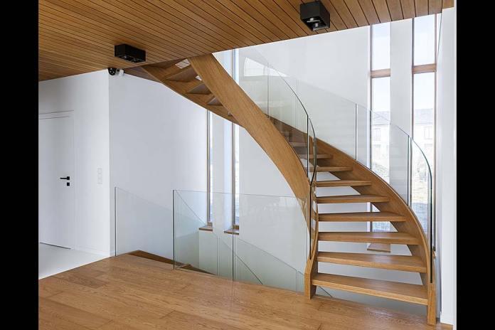 Gięte schody o konstrukcji policzkowej z dębu oraz hartowanego szkła